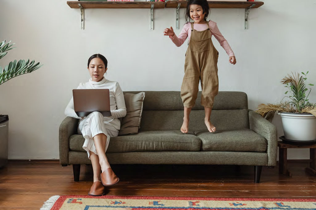 a working mother and daughter on the sofa