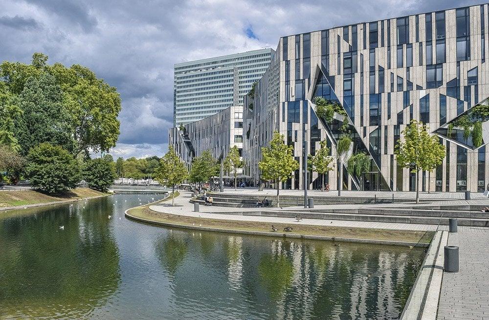 Curvy landscape against angular buildings
